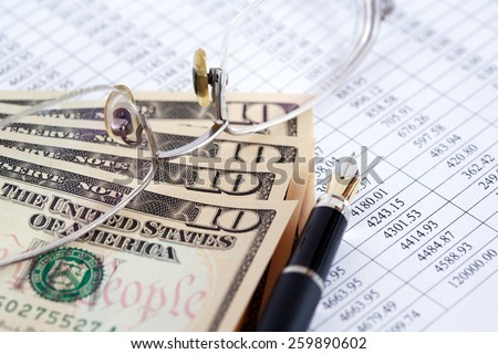 Bookkeeping concept. Closeup of eyeglasses and pen near dollar bank notes on paper list with digits