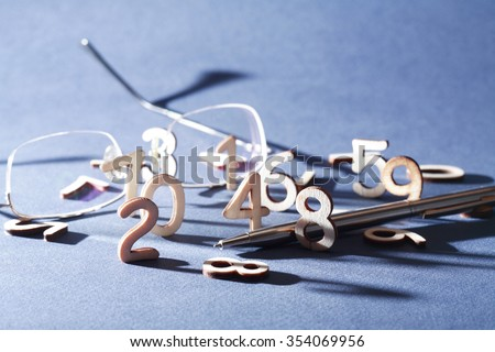 Bookkeeping symbol. Set of wooden digits near pen and spectacles on gray background - stock photo