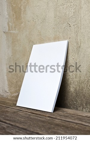 Booklet with white Cover at wooden floor leans at an old wall.  - stock photo