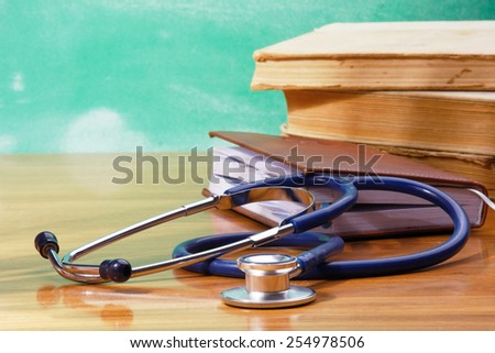 Books, a stethoscope and an organizer on a wooden desk - stock photo