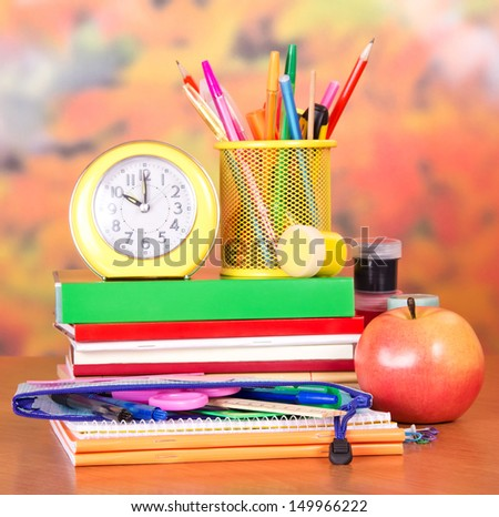 Books, alarm clock, a pencil-case with school accessories, paint and apple, on a table