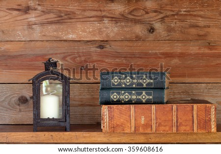 books and a lantern on a shelf - stock photo