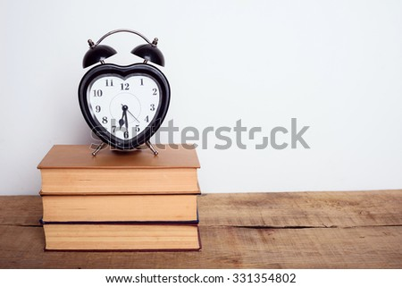 books and alarm clock on wooden background. Education equipment, education concept