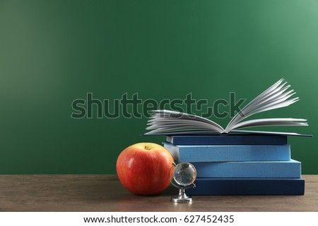 Books And Apple On Chalkboard Background