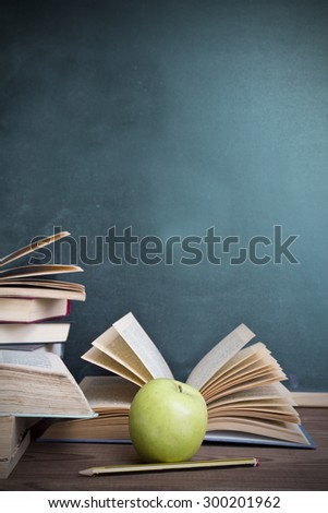books and apple slate background