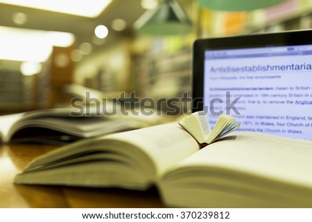Books and computer in a public birary. - stock photo