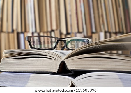 books and glasses on table front of a full bookshelf - stock photo