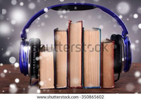 Books and headphones on grey background  over snow effect - stock photo