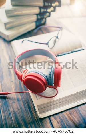 Books and headphones on wood table. vintage effected photo. - stock photo