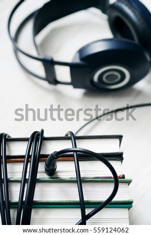 Books and headphones on wooden white surface. Concept of listening to audio-books.