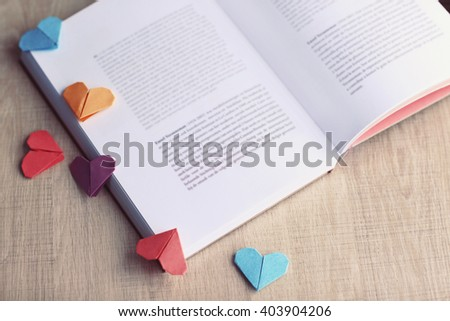 Books and heart shaped bookmarks on a light wooden background - stock photo