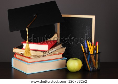 Books and magister cap against school board on wooden table on grey background - stock photo