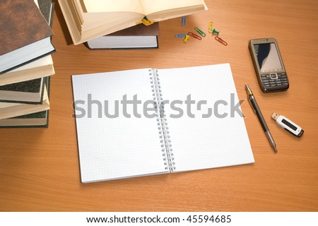 Books and mobile phone on wooden desktop. - stock photo