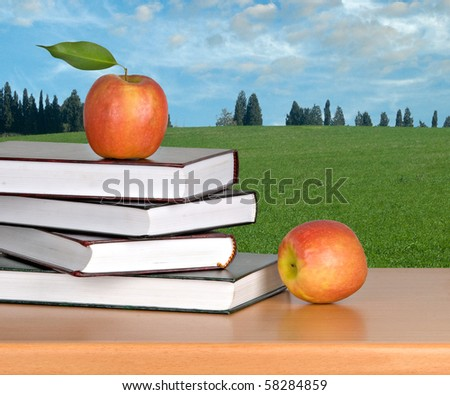 Books and red apples on desk