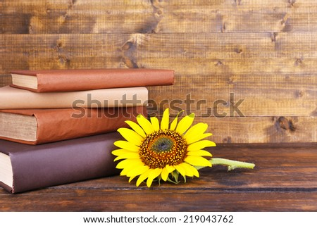 Books and sunflower on wooden table on wooden wall background - stock photo