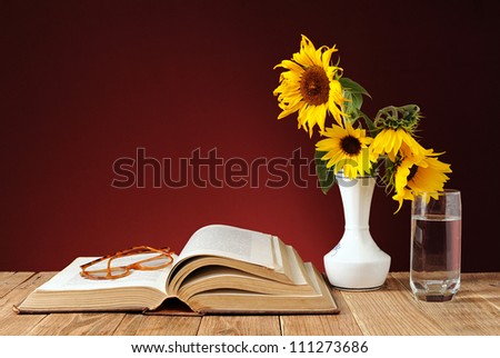 Books and sunflowers in a vase on the table