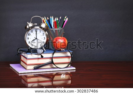 Books, apple, alarm clock and pencils on wood desk table and black board. Back to school concept - stock photo