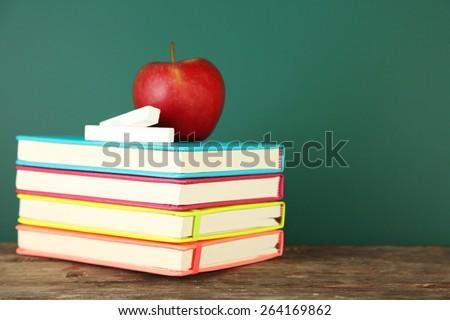 Books, apple and chalk on blackboard background - stock photo