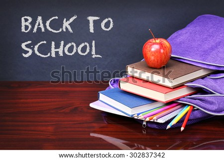 Books, apple, backpack and pencils on wood desk table. Text back to school on black board concept - stock photo