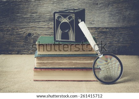 books, camera, and magnifying glass on retro background with Instagram Style Filter - stock photo