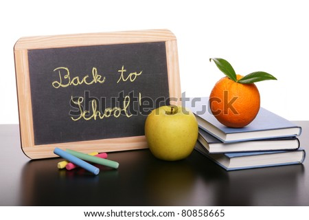 Books, chalkboard and fruit for school