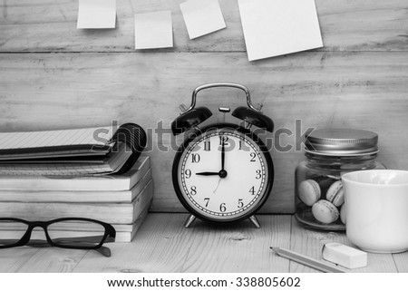 books , glasses, clock ,macaroons and a cup of coffee on workplace desktop , black and white  - stock photo