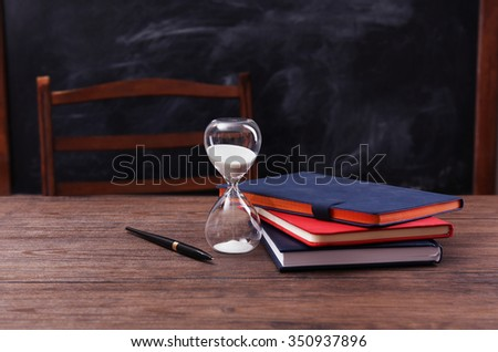 Books, hourglass and pen on wooden table - stock photo