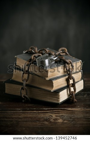 Books locked up with chains and a padlock. - stock photo
