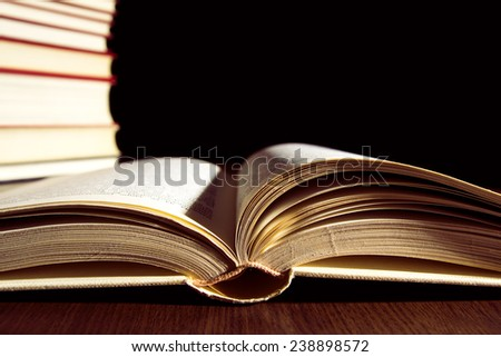 Books on a wooden table on a black background