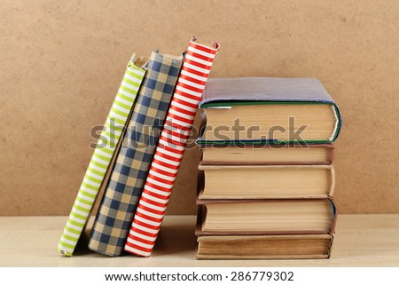 Books on shelf, close-up, on wooden background - stock photo
