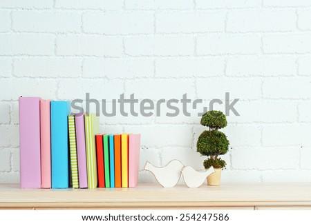 Books on shelf on wall background - stock photo