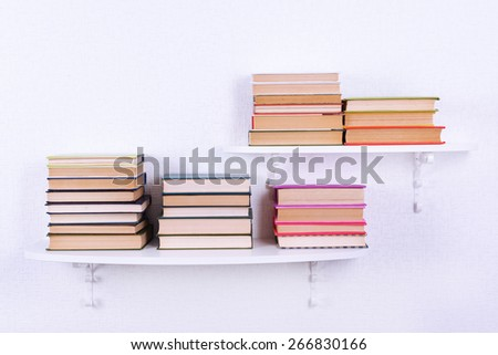 Books on shelves on white wall background