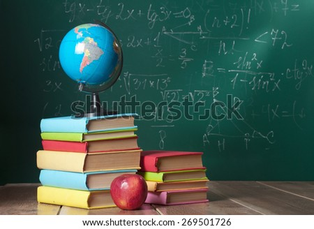 Books on the background of the school board - stock photo
