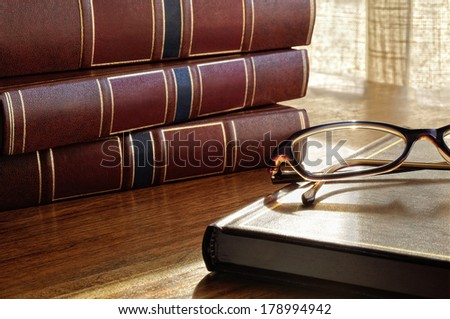 books on the table and glasses and the bottom window and curtains - stock photo