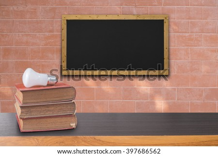 books on wooden table and  black board on brick wall texture background