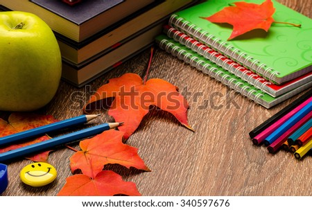 Books, pencils, notebooks, autumn red leaves and green apple on a table - stock photo