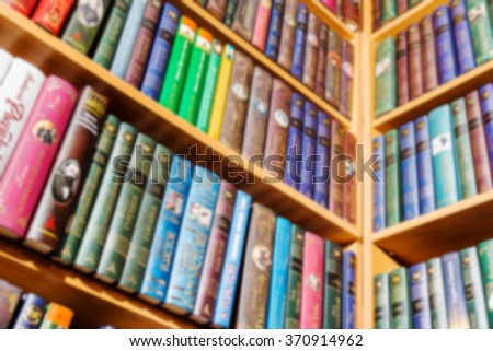 books standing on the angular bookshelf. blurred image - stock photo