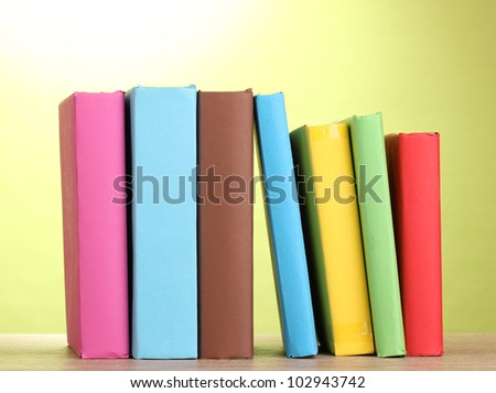 Books staying on wooden table on green background - stock photo