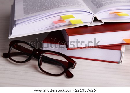 Books with bookmarks and glasses on wooden table - stock photo
