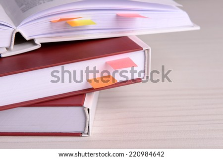 Books with bookmarks on wooden table - stock photo