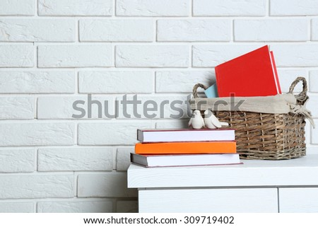 Books with decorative basket on brick wall background - stock photo