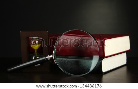 books with magnifying glass on table on black background - stock photo