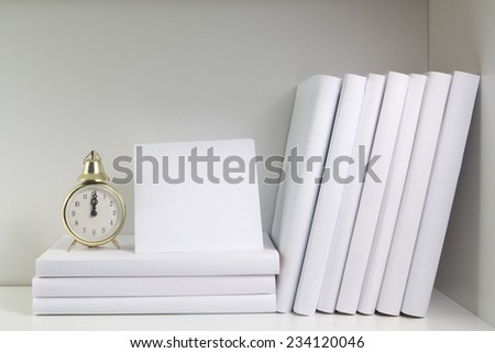 Bookshelf and books in white color, card with pace for text and watch - stock photo