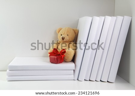 Bookshelf and books in white color, teddy bear with gift - stock photo