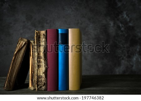 Bookshelf with old and new books - history of books - stock photo