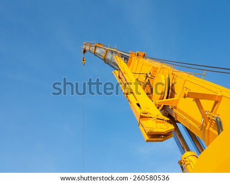 Boom of mobile crane with blue sky background. - stock photo