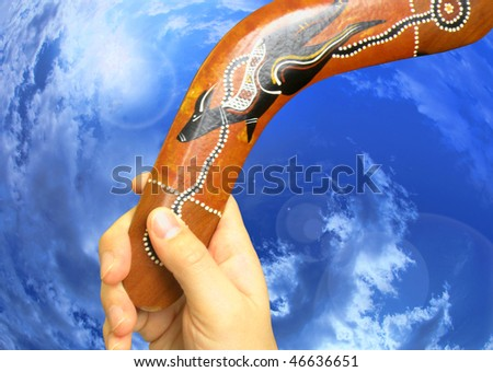 boomerang in hand on the sky background - stock photo