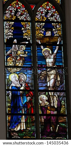 BOORTMEERBEEK, BELGIUM - JULY 6:  Stained Glass window depicting Jesus on the cross  in the church of Boortmeerbeek, Belgium, on July 6, 2013. - stock photo