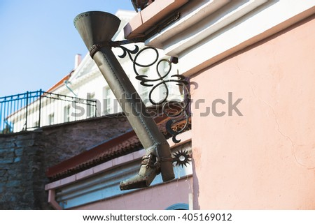 Boot like downtake tube in street of old town in Tallinn, Estonia