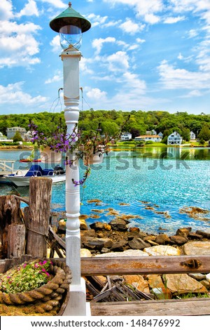 Boothbay, Maine waterfront on a sunny summer day with a wooden lamppost and hanging flower baskets in the foreground. The area is a popular destination for tourists visiting New England. - stock photo